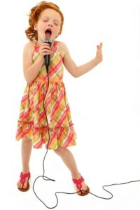 little girl singing into microphone